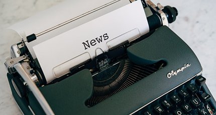 A typewriter with paper that says 'News'